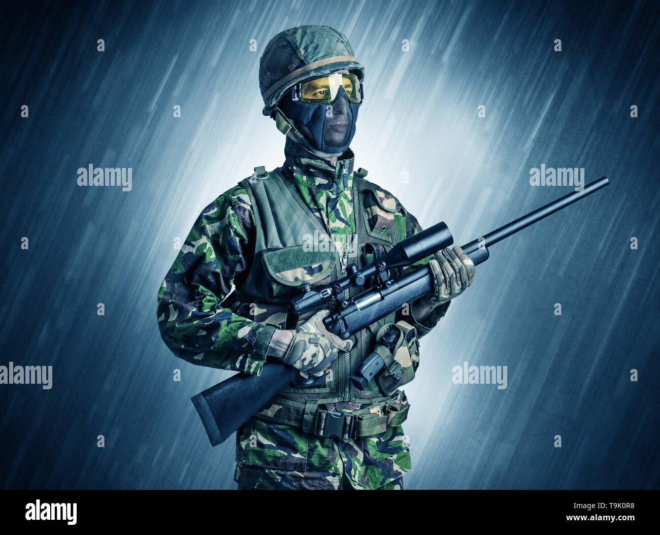 Armed soldier standing in rainy weather  - Stock Image