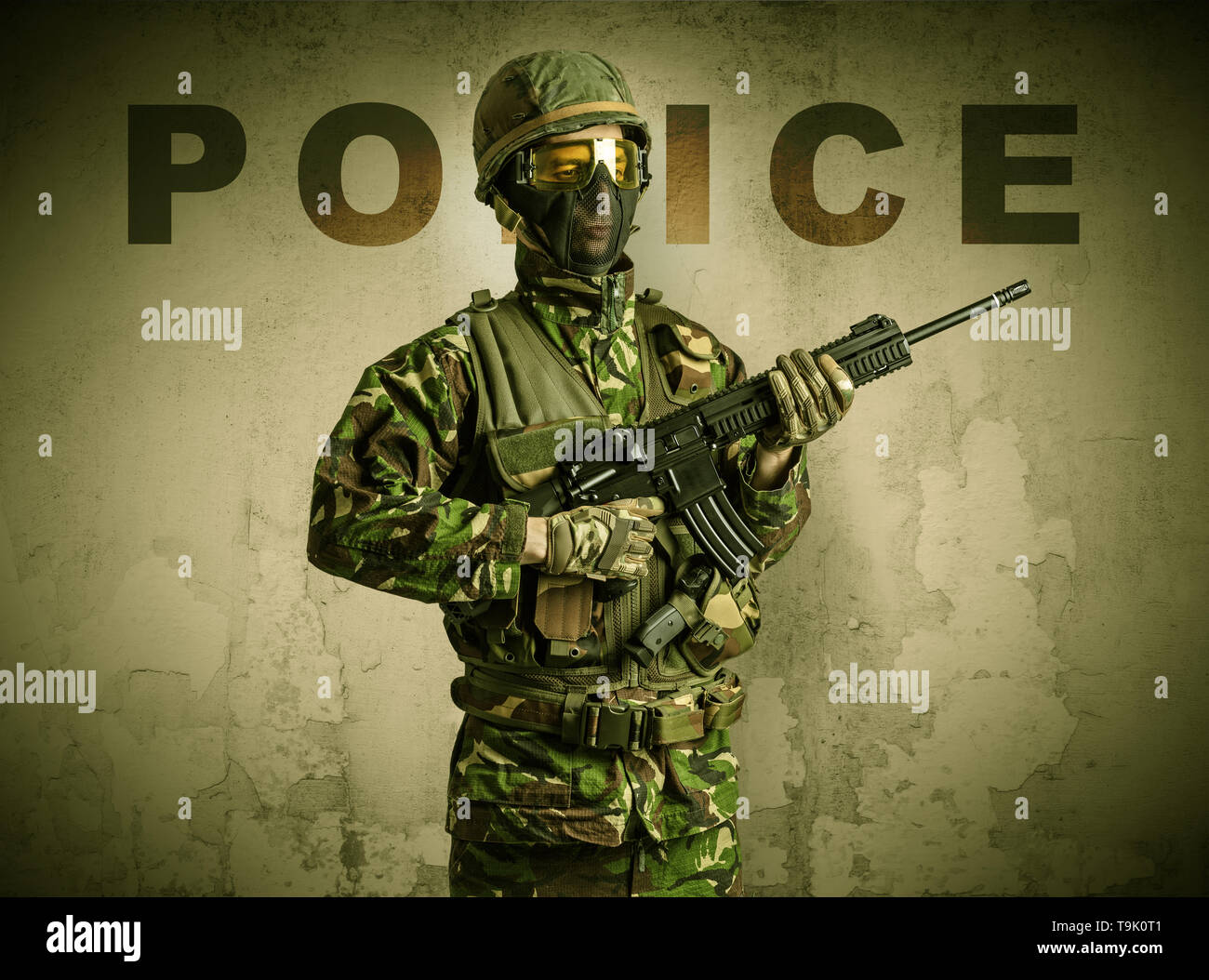 Uniformed armed soldier with damaged wall background  - Stock Image