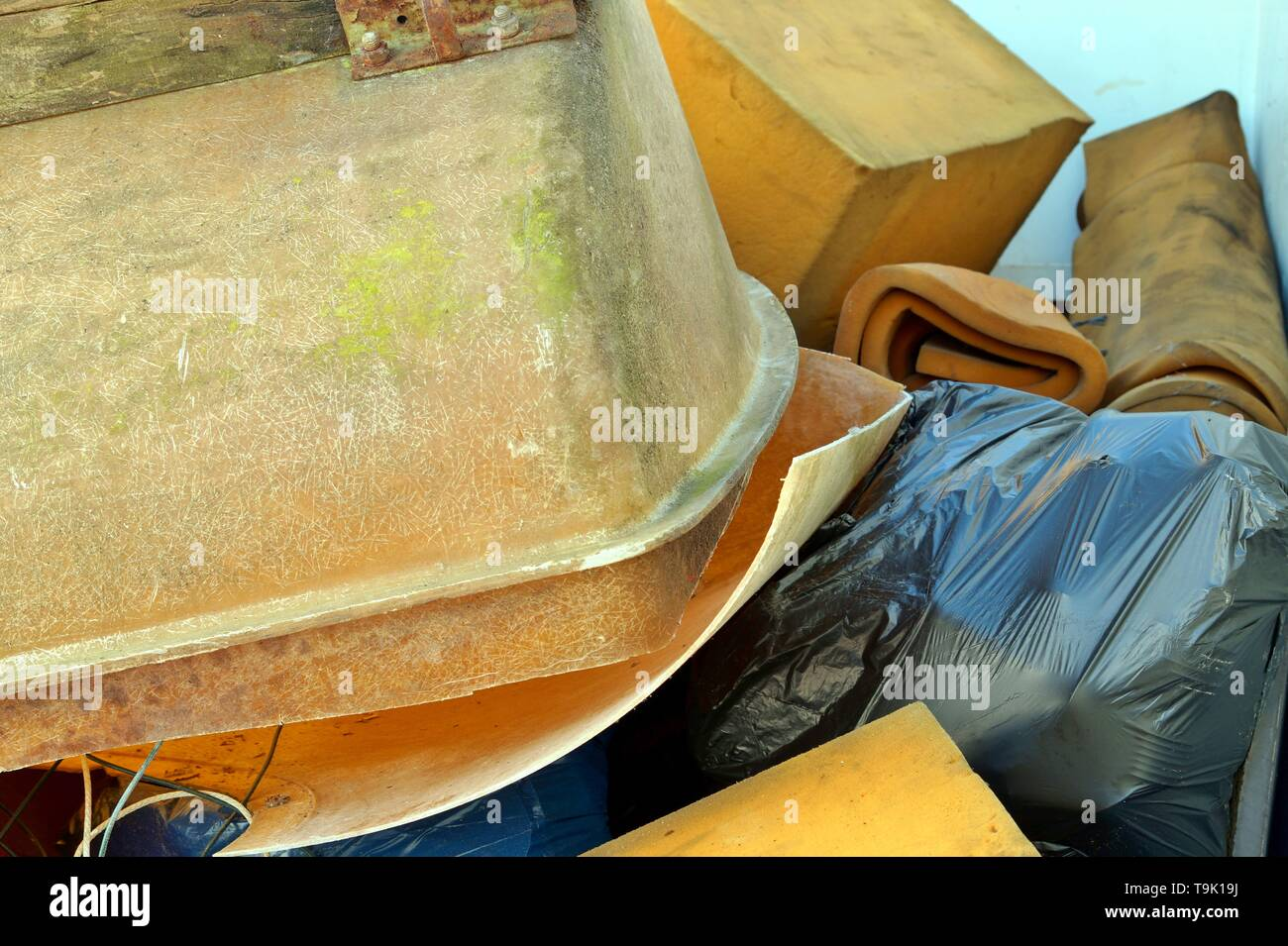 Large amount of used Foam base and old bathtub about to be recycled. Waste Disposal concept for consumerism, modernization, digital age, urbanization, - Stock Image