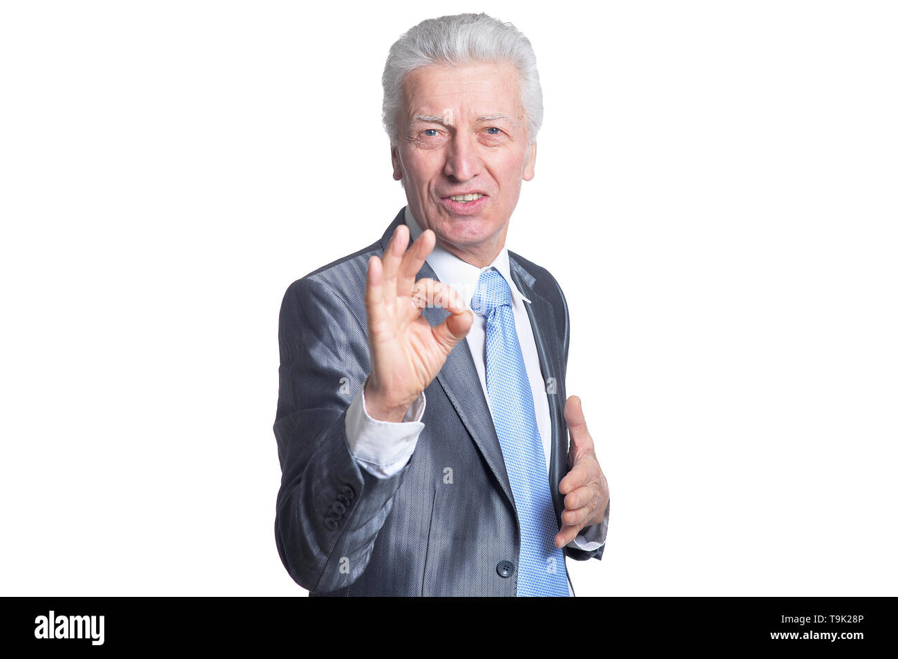 Smiling senior businessman showing ok sign against white - Stock Image