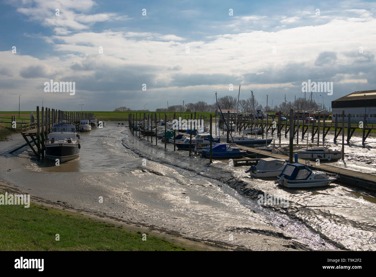 Boats are in the mud at low tide and a setting sun shines in the mud - Stock Image