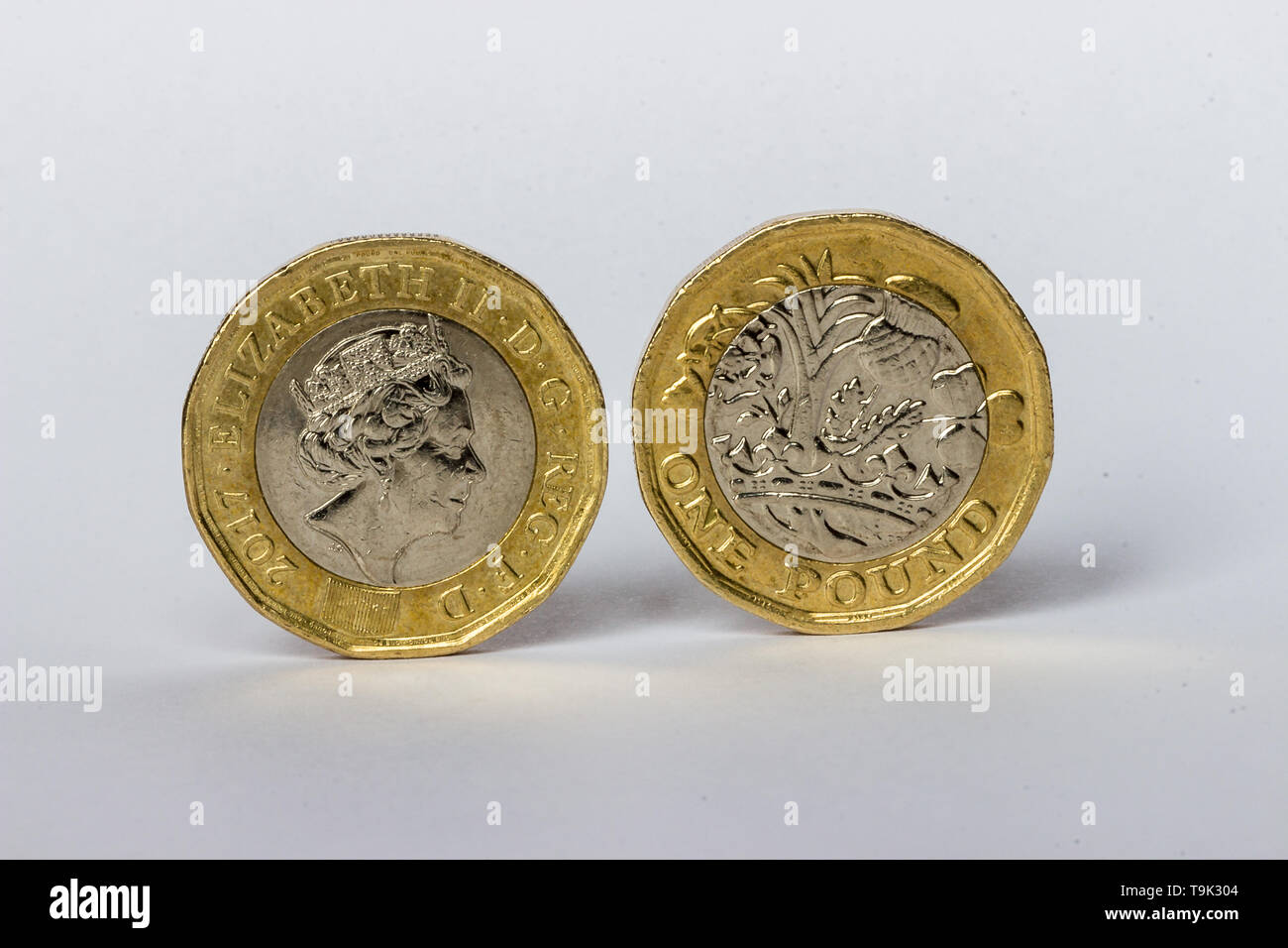 Pair of £1 coins standing on edge. - Stock Image