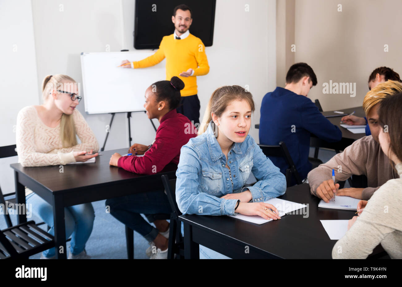 Smiling classmates working in groups to complete task during class - Stock Image