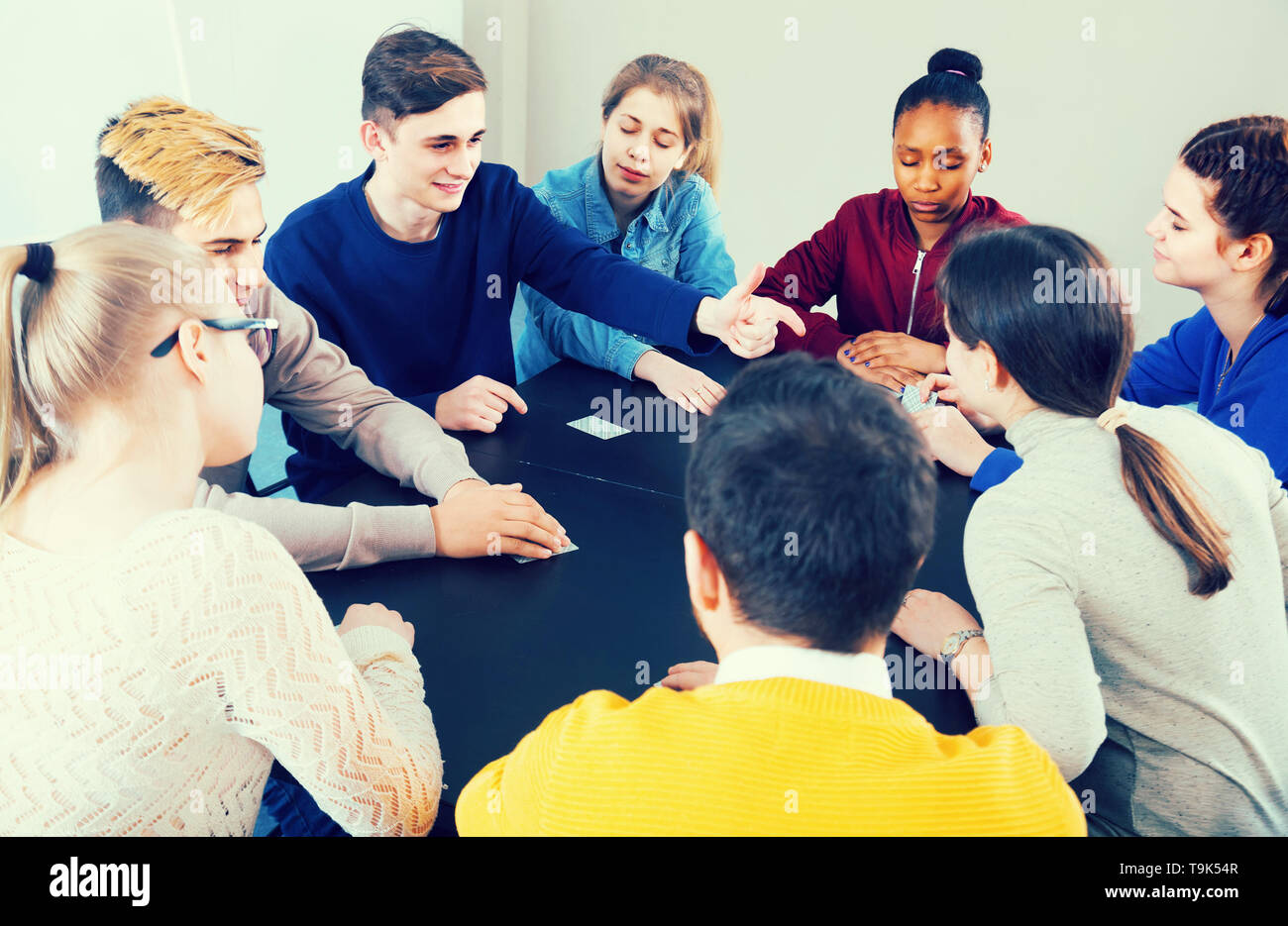 positive american classmates having round of Werewolf game at break between classes - Stock Image