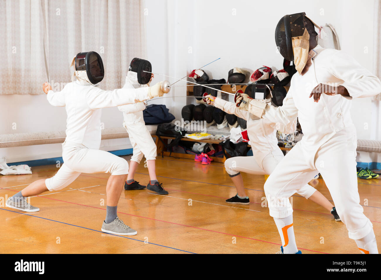 Cheerful group practicing effective fencing techniques in