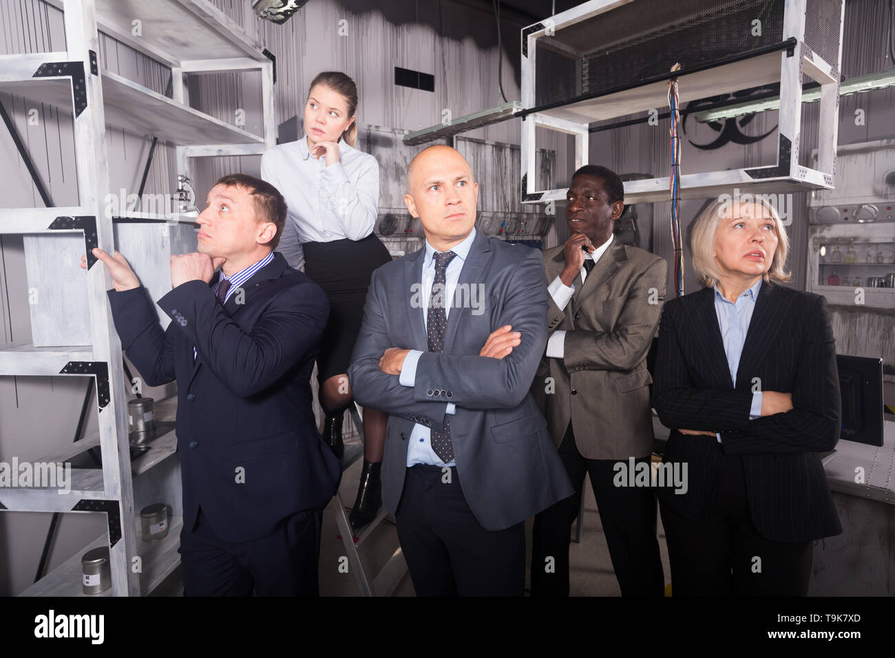 Five pensive adults businesspeople solving conundrums in quest room in view as abandoned lab during corporate event - Stock Image