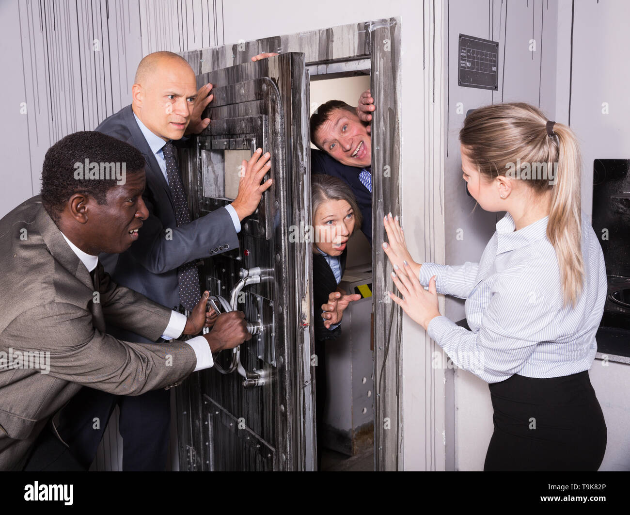 Businesspeople having fun on corporate event in quest room stylized as underground shelter. With expression of panic they holding door so others will  - Stock Image