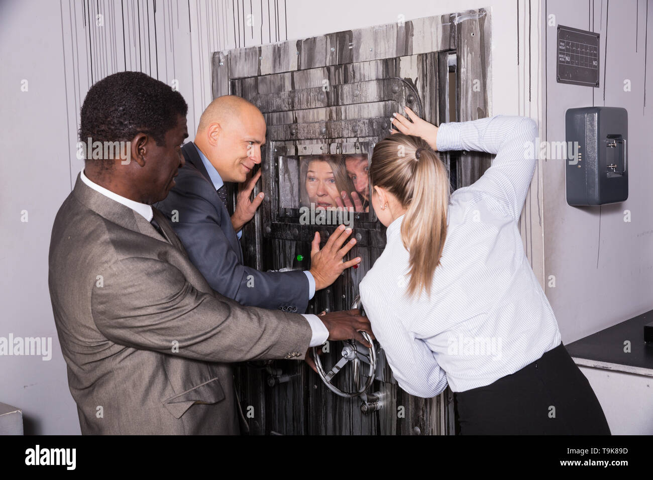 Scared businesspeople trying not to let others into quest room, shutting door. Concept of fear of competition - Stock Image