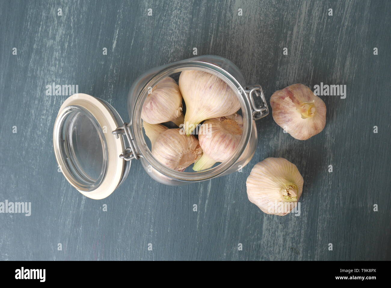 Heads of garlic in a kilner jar on a blue distressed wood kitchen table. - Stock Image