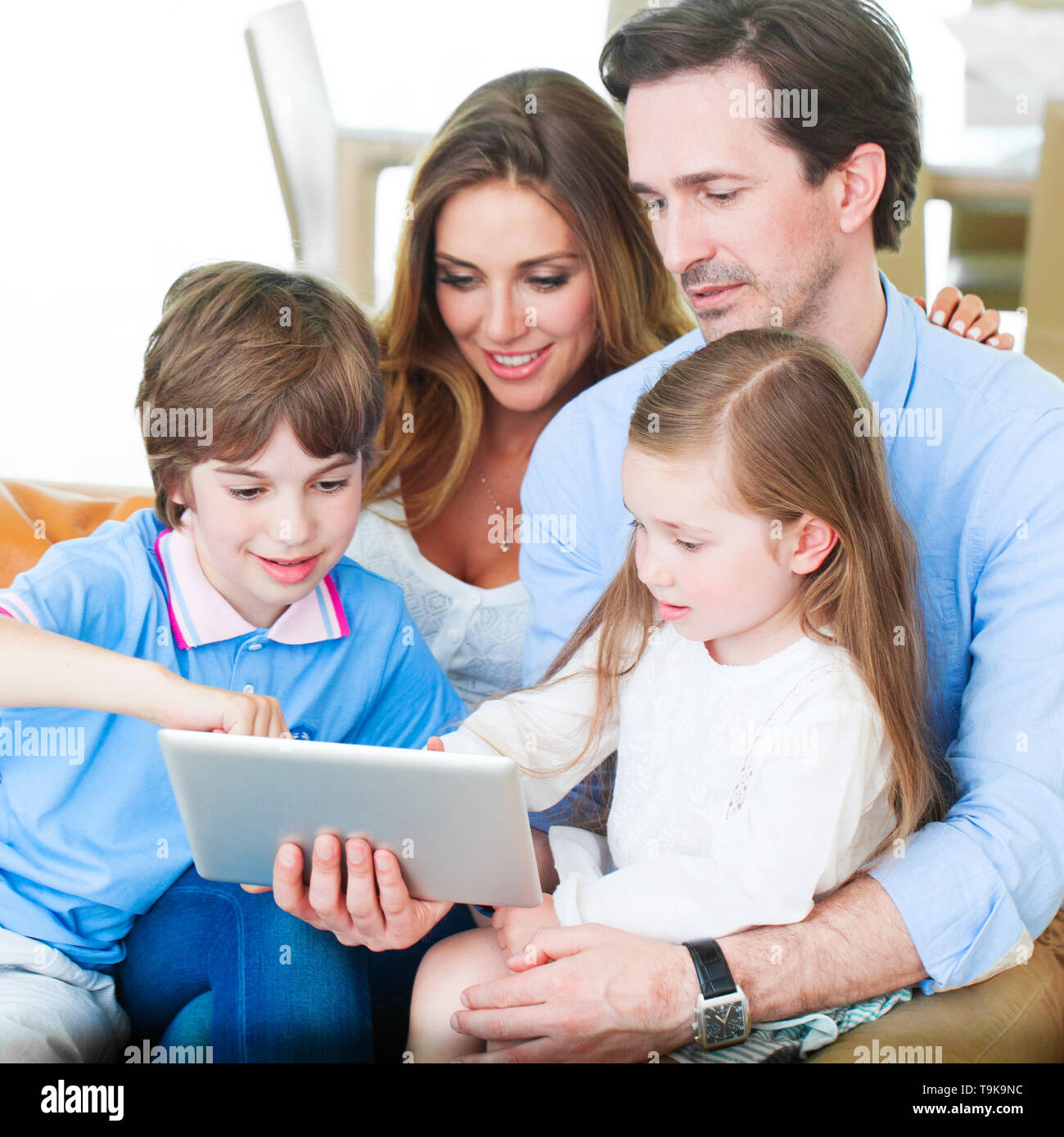 Portrait of happy family with two children sitting on sofa and using digital tablet pc - Stock Image