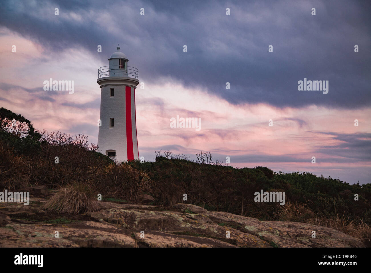 White and red lighthouse at Mersey Bluff Devonport on a cloudy winter morning at sunrise - Stock Image