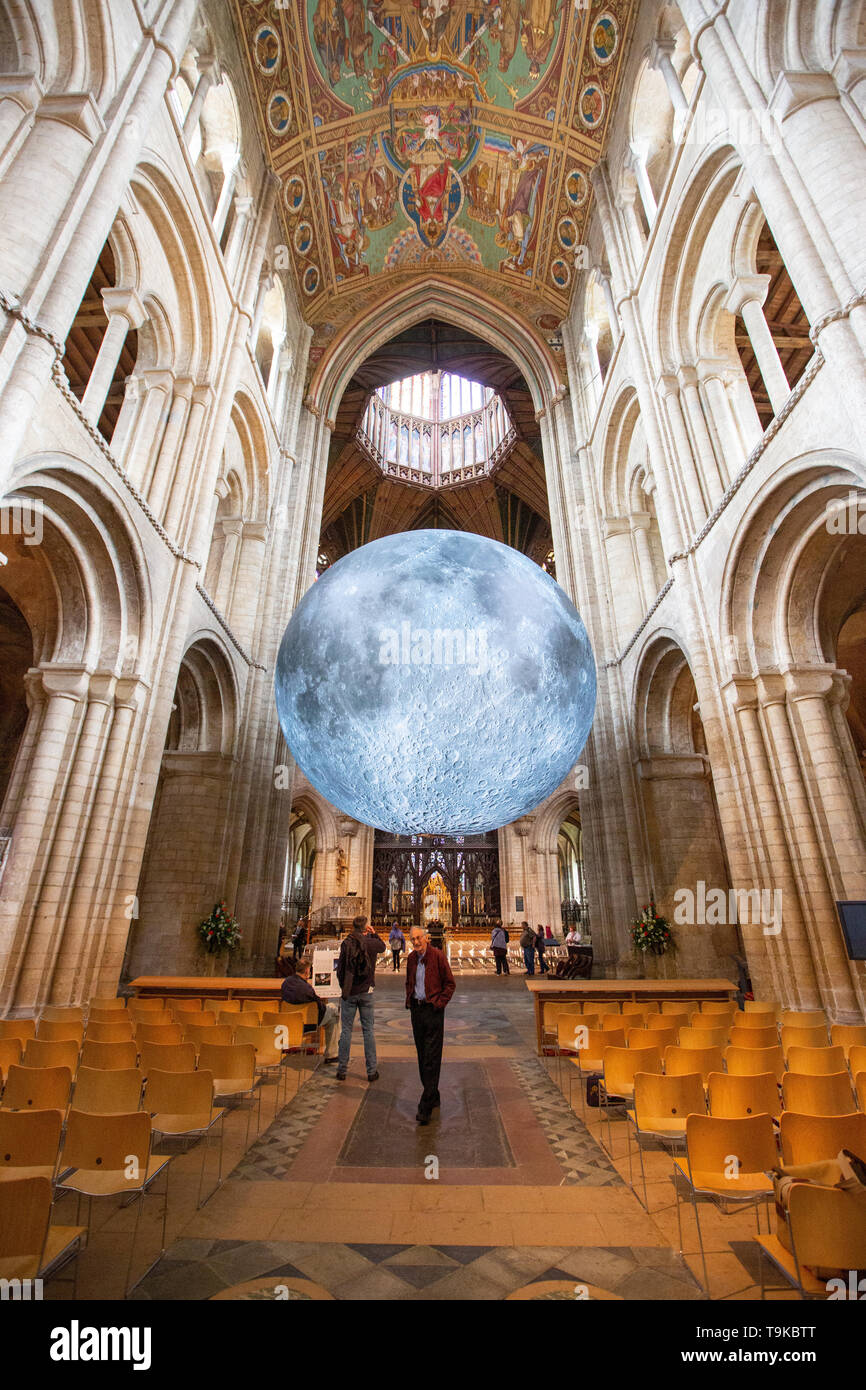 Picture dated May 18th shows the Moon installation in Ely Cathedral in Cambridgeshire by UK artist Luke Jerram  which has been installed for the science festival which opened this weekend.  A huge art installation of the MOON measuring SEVEN METRES in diameter is hanging in historic Ely Cathedral in Cambridgeshire as part of its science festival.  The impressive Museum of the Moon is a touring artwork by UK artist Luke Jerram and will be at the Gothic-style cathedral until June 9.  The moon features detailed 120dpi detailed NASA imagery of the lunar surface and at a scale of about 1:500,000, - Stock Image