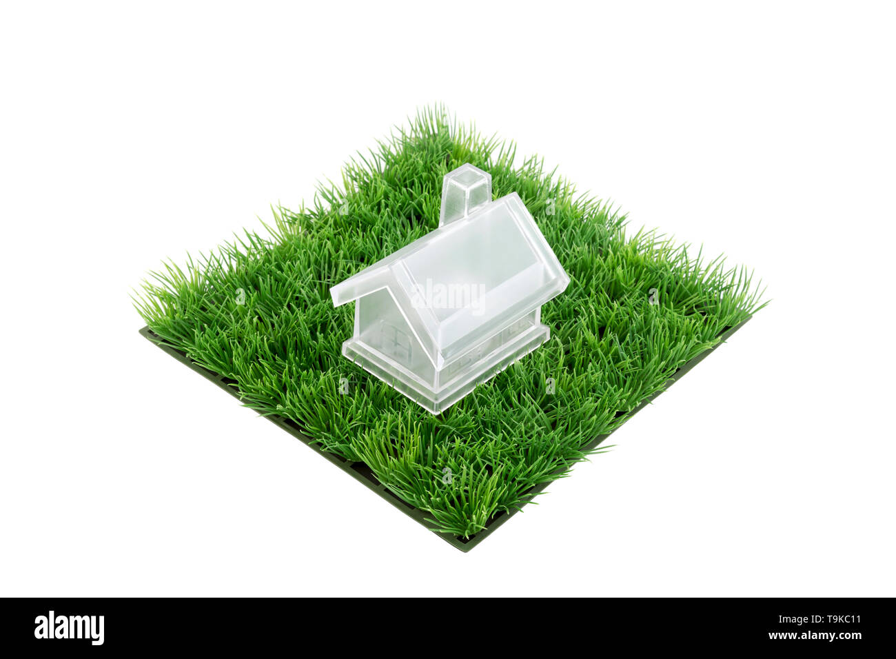 Crystal house on square of green grass field isolated on white background - Stock Image