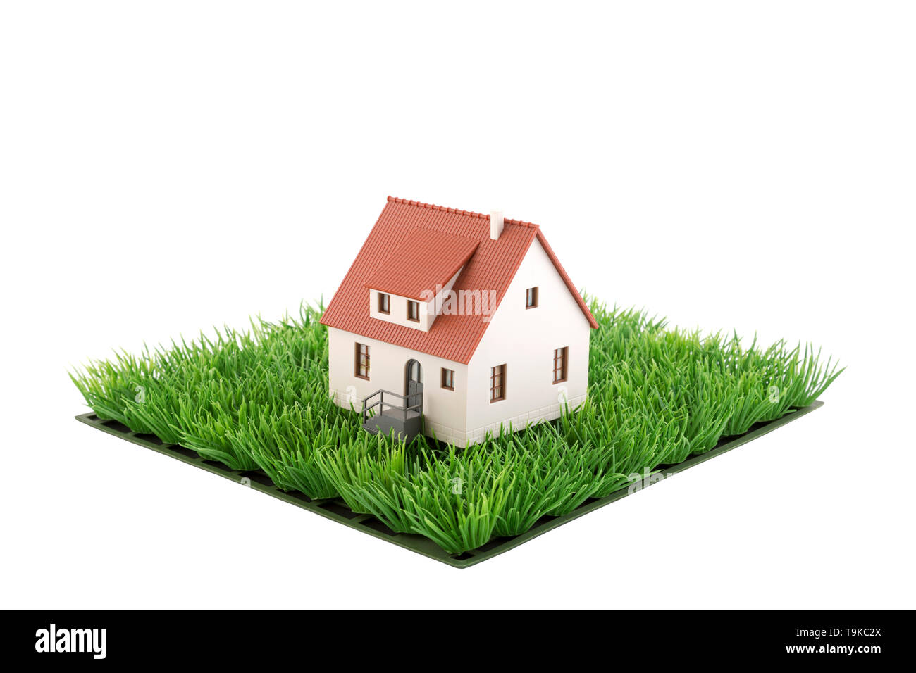House miniature on square of green grass field isolated on white background - Stock Image