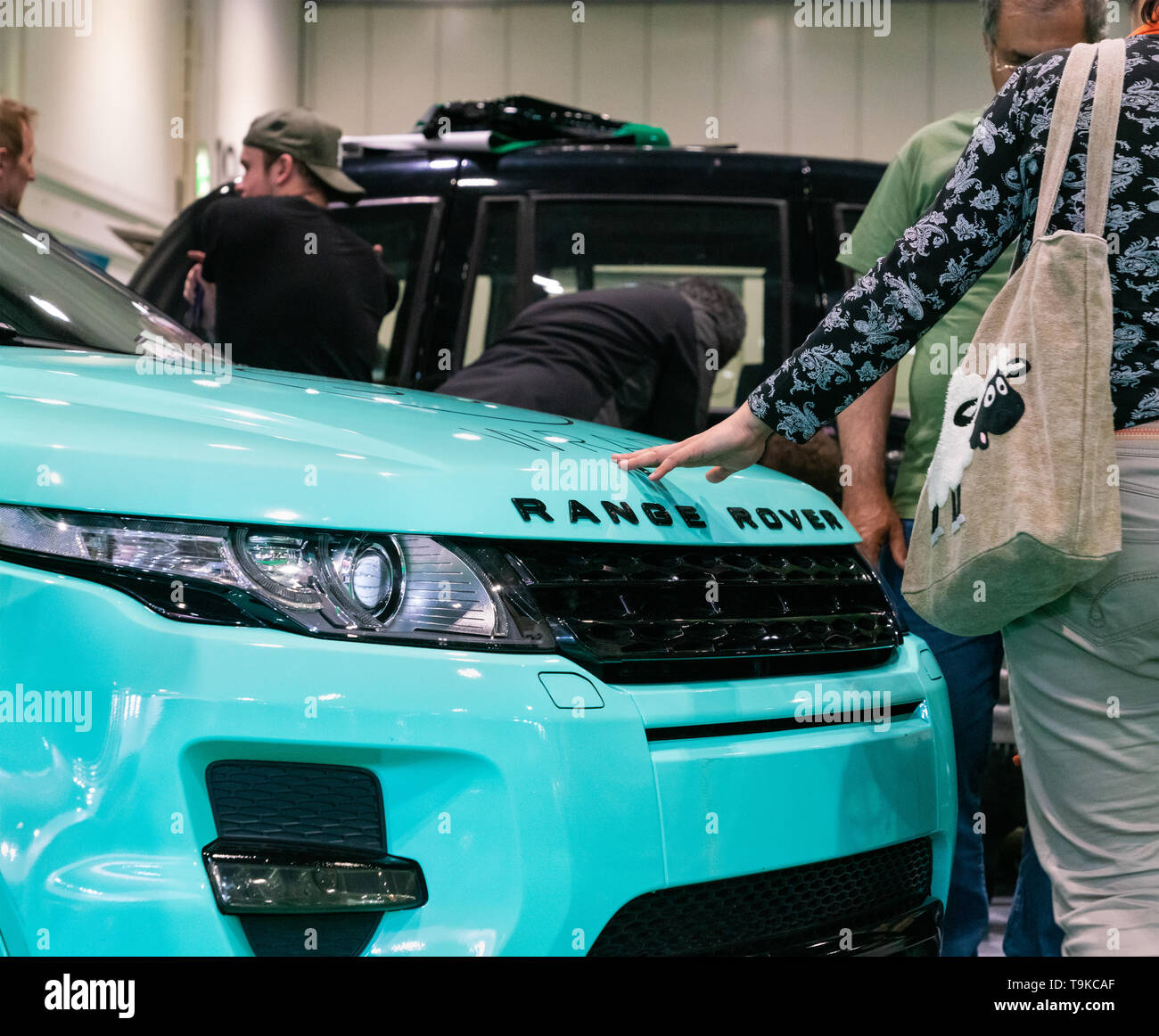 18th May 2019. London, UK. A woman touches elegant Range Rover Evoque model at London Motor Show 2019. - Stock Image