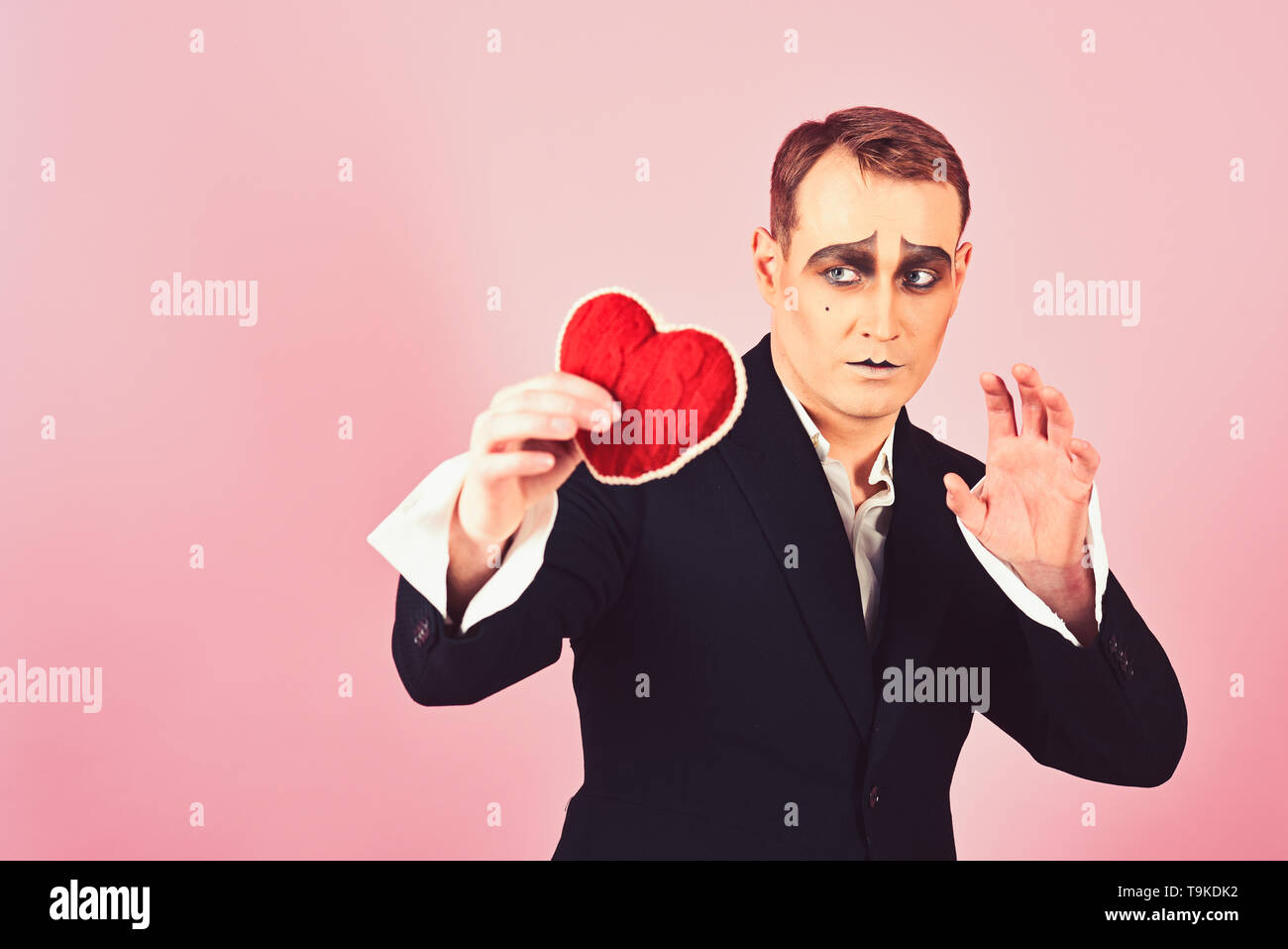 His story of boundless love. Theatre actor pantomime falling in love. Mime actor with love symbol. Mime man hold red heart for valentines day. Love - Stock Image