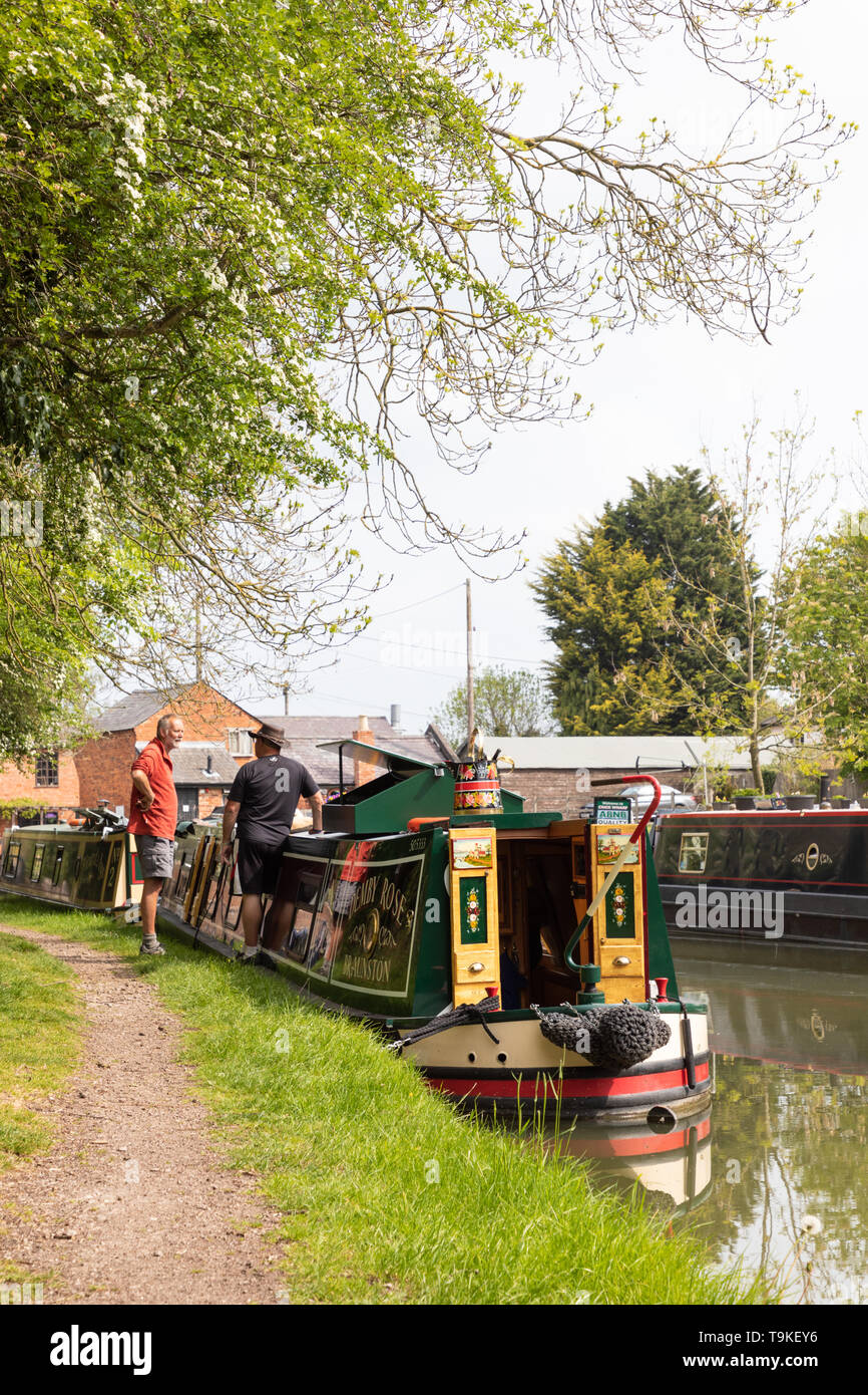 Two men stand talking on a canal towpath next to a brightly painted narrowboat. They have moored their boats in readiness for the Crick Boat Show. - Stock Image
