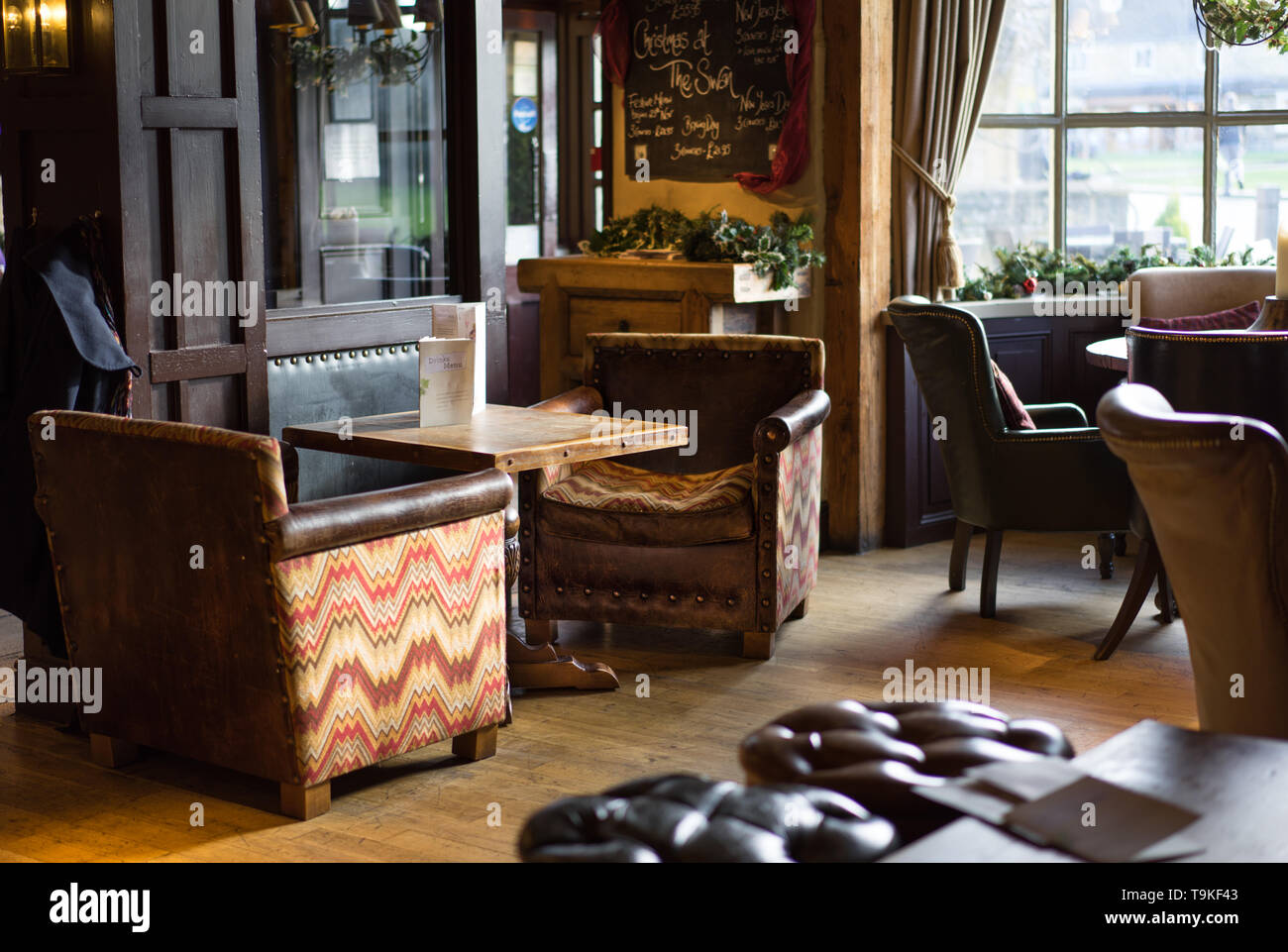 Interior of the Swan public House and hotel in Broadway with comfy old leather chairs and wooden panelling - Stock Image