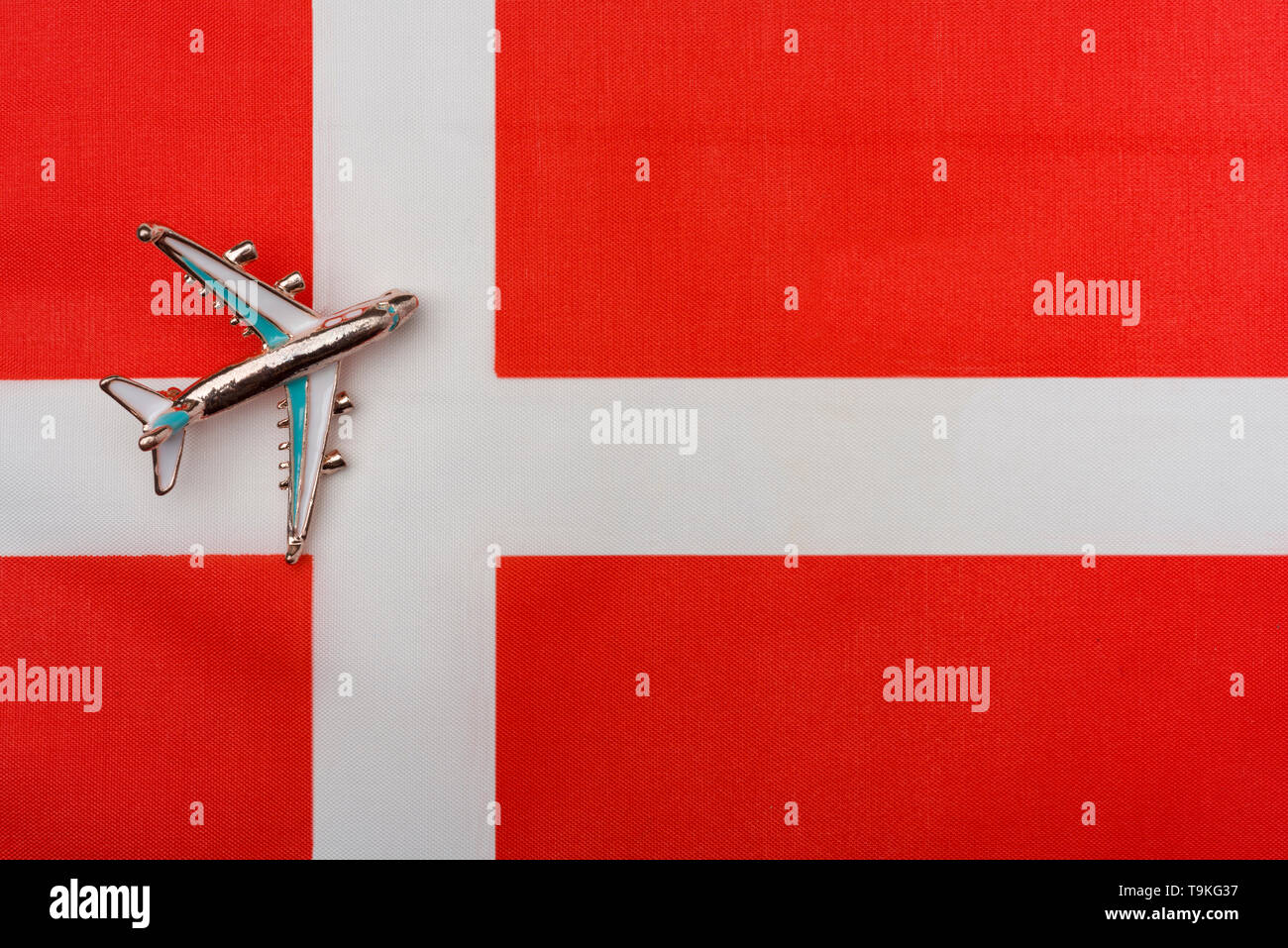 Plane over Denmark flag travel concept. Toy plane on the flag in the background. - Stock Image