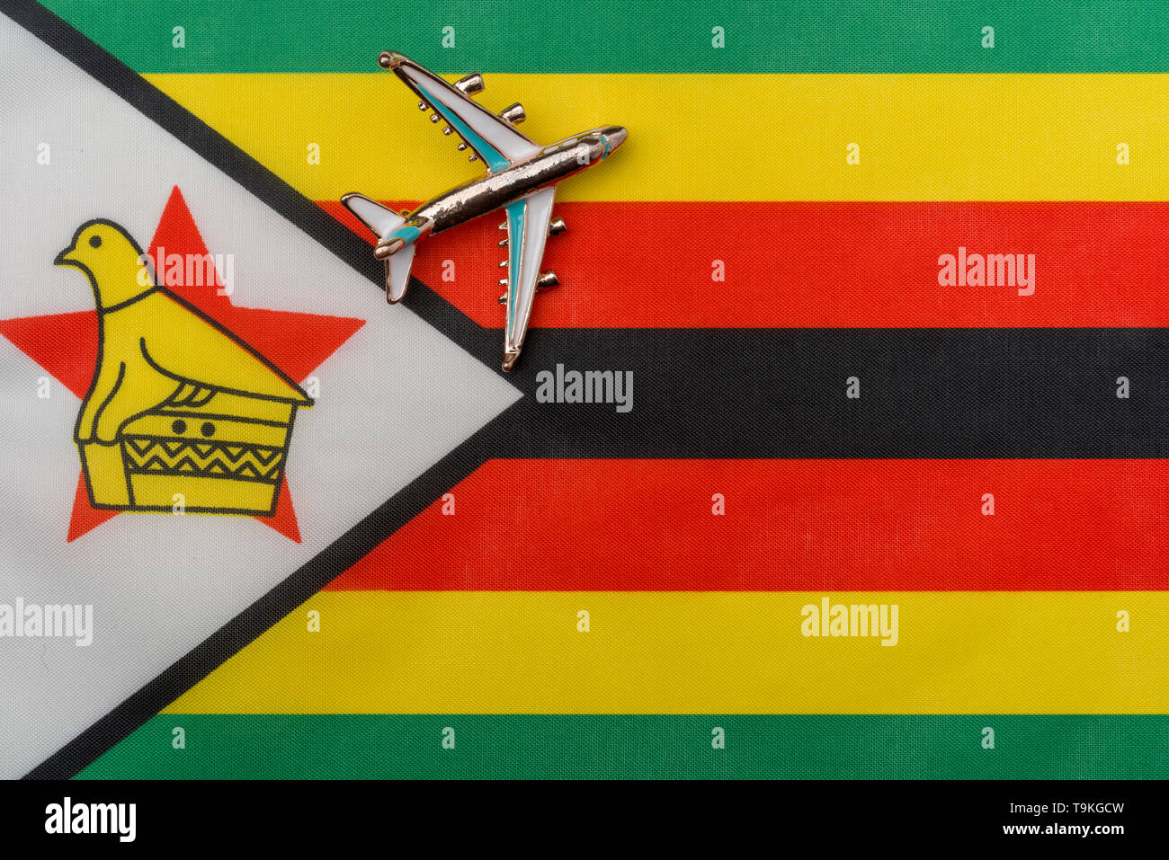 Plane over the flag of Zimbabwe the concept of the journey. Toy plane on the flag in the background. - Stock Image