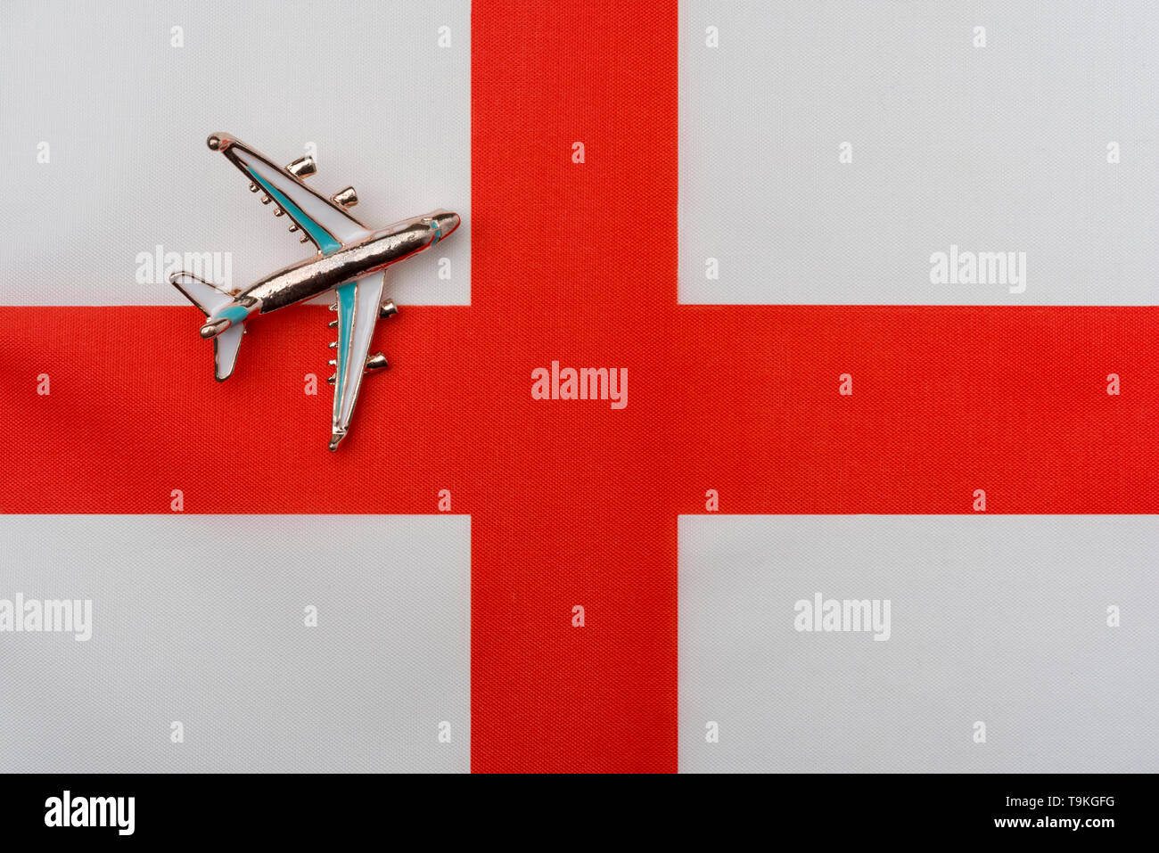 Plane over the flag of the English Kingdom travel concept. Toy plane on the flag in the background. - Stock Image