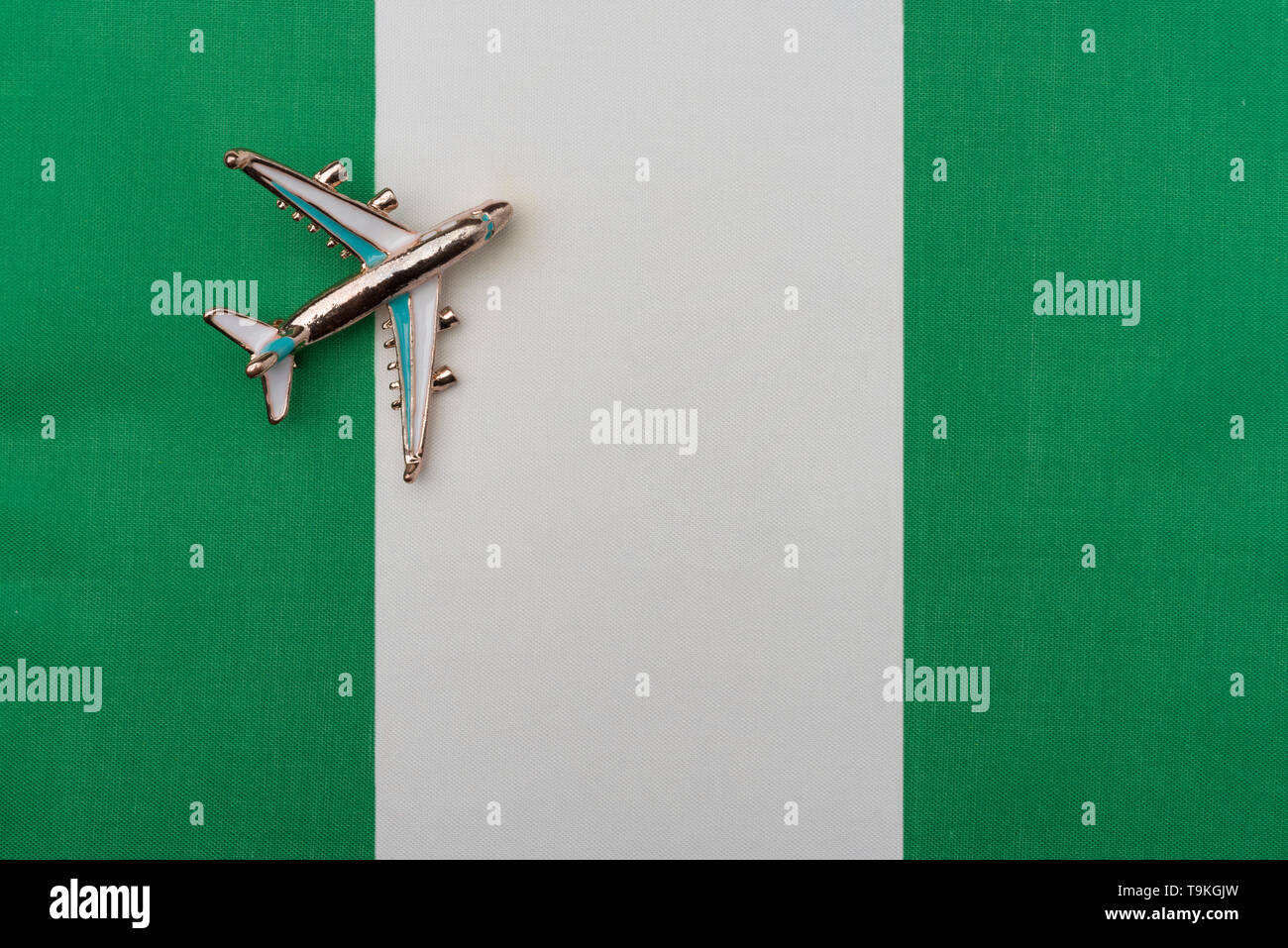 Plane over the flag of Nigeria travel concept. Toy plane on the flag in the background. - Stock Image
