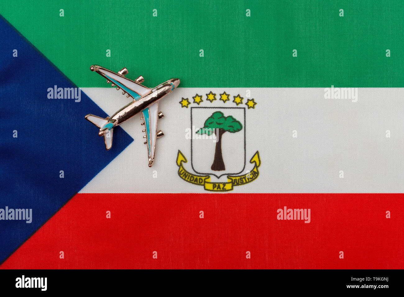 Plane over the flag of Equatorial Guinea travel concept. Toy plane on the flag in the background. - Stock Image