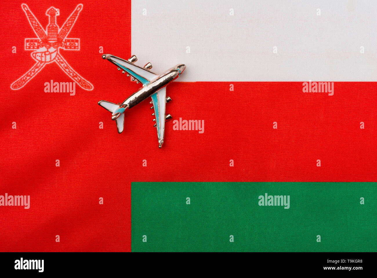 Plane over the flag of Oman travel concept. Toy plane on the flag in the background. - Stock Image