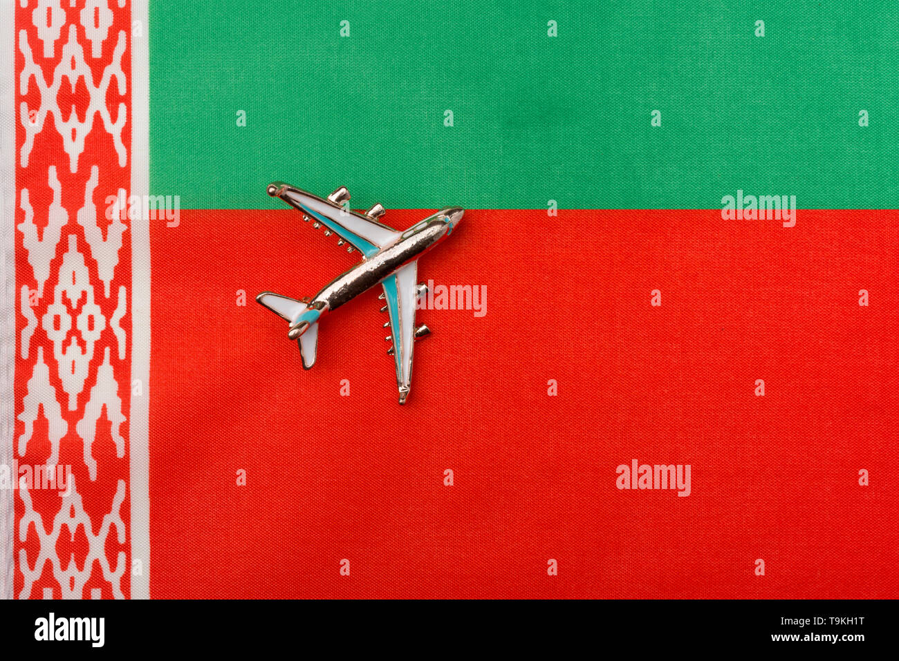 Plane over the flag of Belarus travel concept. Toy plane on the flag in the background. - Stock Image