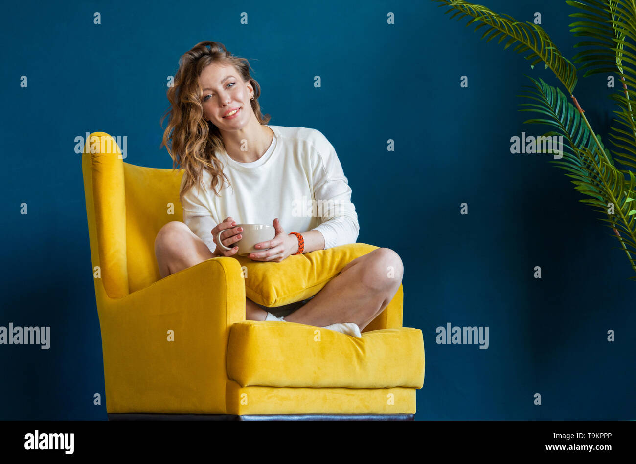 Young blonde woman reading book at home, drinking coffee or tea and sitting in yellow armchair. Cozy and comfortable timespending. - Stock Image