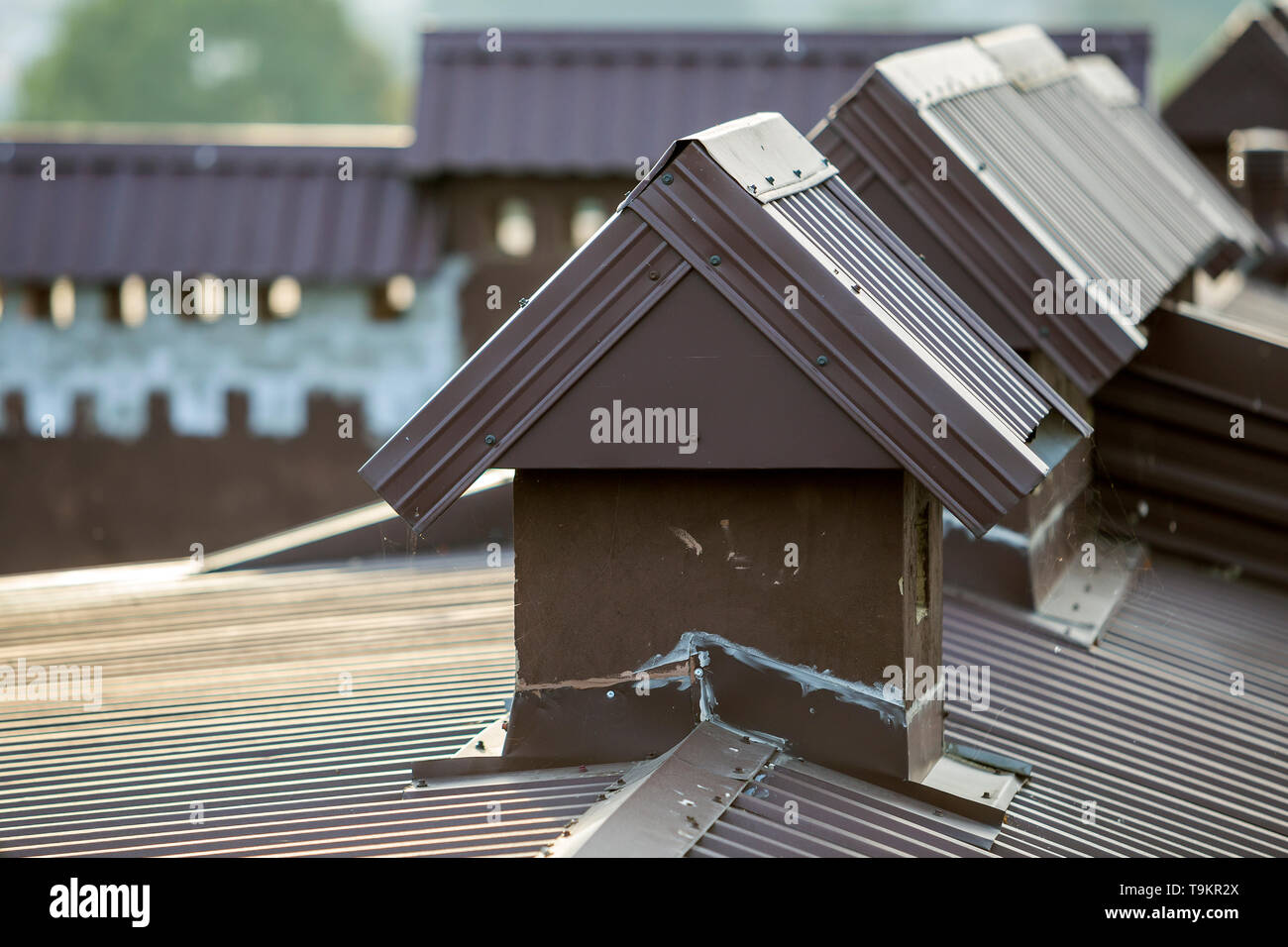 Close-up detail of new built brick plastered chimneys on house top with metal tile roof. Roofing, repair and renovation work. - Stock Image