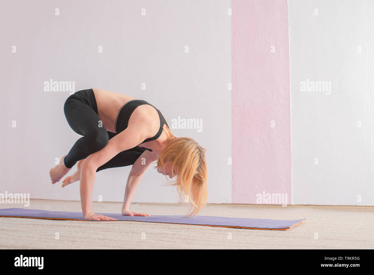 The girl in black sportswear is doing yoga in the gym on the mat. Copy space. - Stock Image