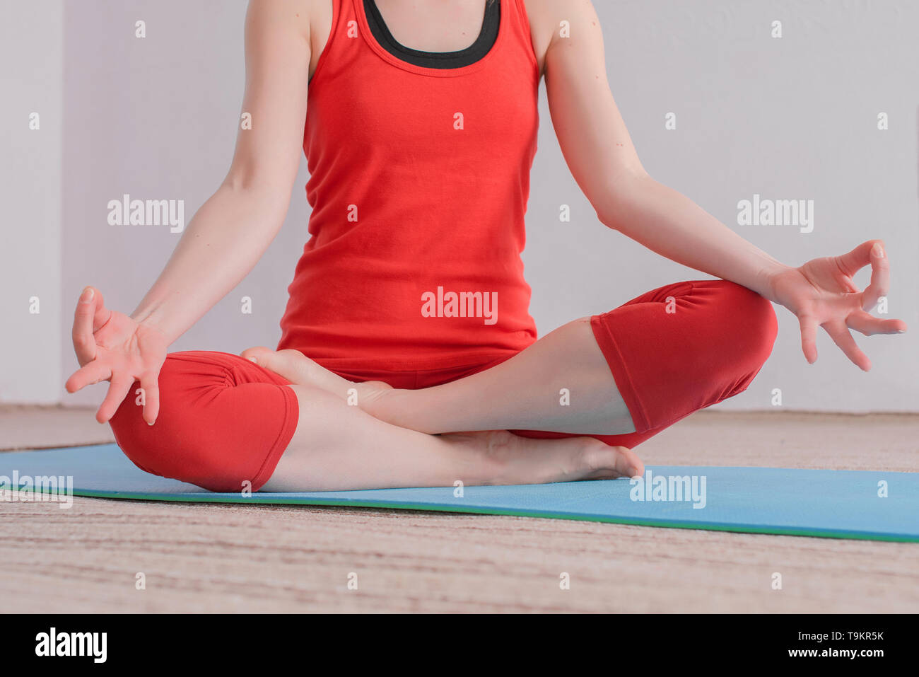 A girl in a red sports uniform sits in a lotus position during yoga in the hall. The girl makes mudras hands. - Stock Image