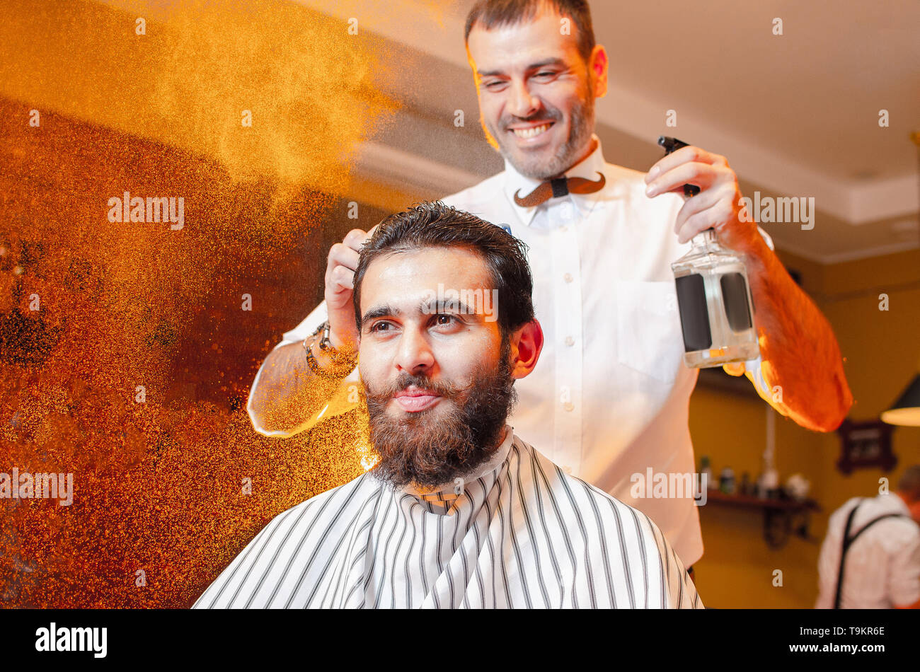 Barber combs his hair to a young guy with a beard and mustache and sprinkles hair on the spray gun. Barber Shop. - Stock Image