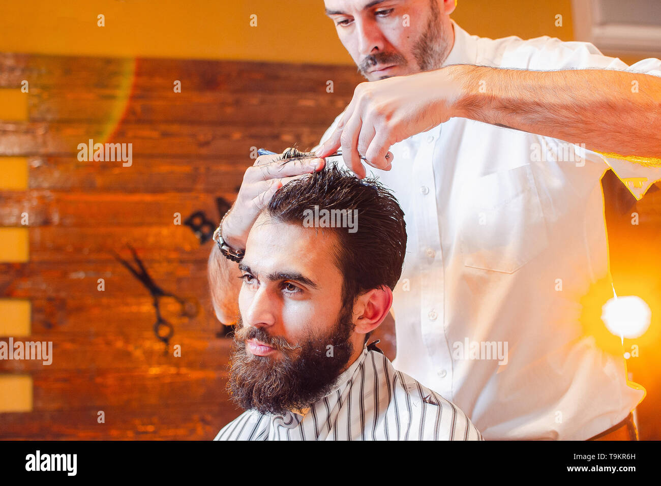 Barber shears hair on her head with a young handsome guy with a beard and mustache. Barber Shop. - Stock Image
