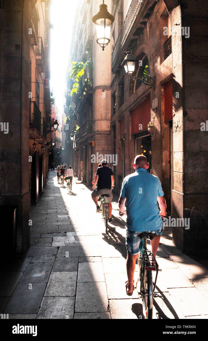 Group of cyclists on the narrow street of Barcelona, sunlight shines through the narrow space between the houses. - Stock Image