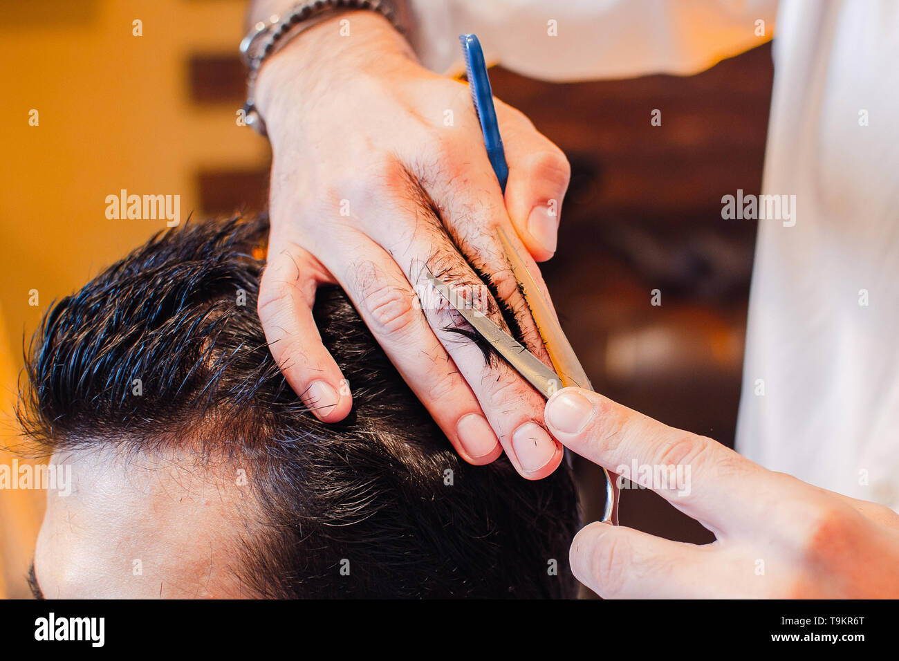 Barber shears the hair on her head with scissors. Haircut close-up. Barber Shop. - Stock Image