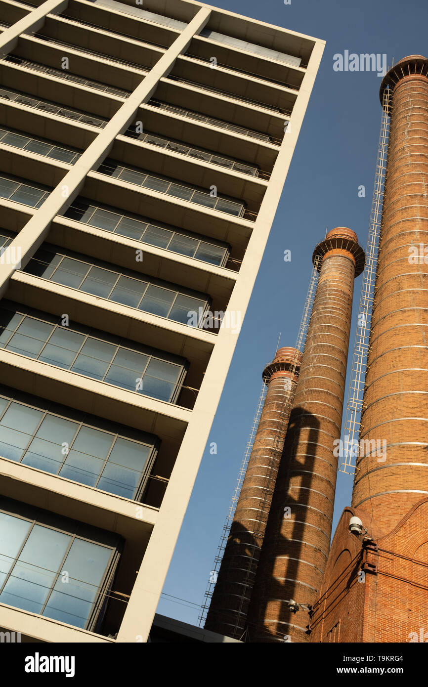 View from below of three red brick chimneys forming part of an old industrial complex in the popular district of Poble Sec, Barcelona, Catalonia, Spai - Stock Image