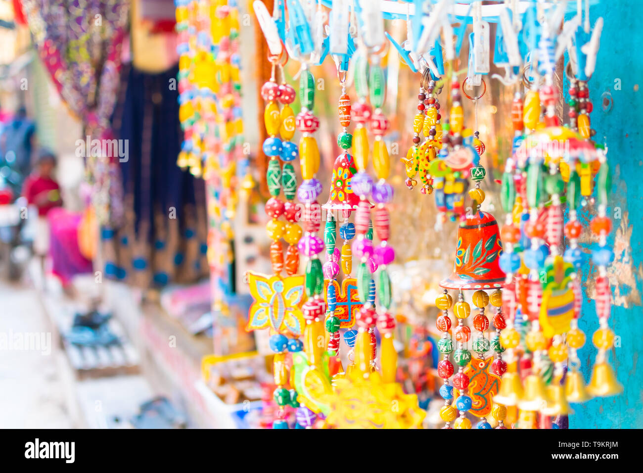 Small bells are hanging at the souvenir shop in Varanasi with a Swastika at the top that represents the positive energy. Hanging decoration items in - Stock Image