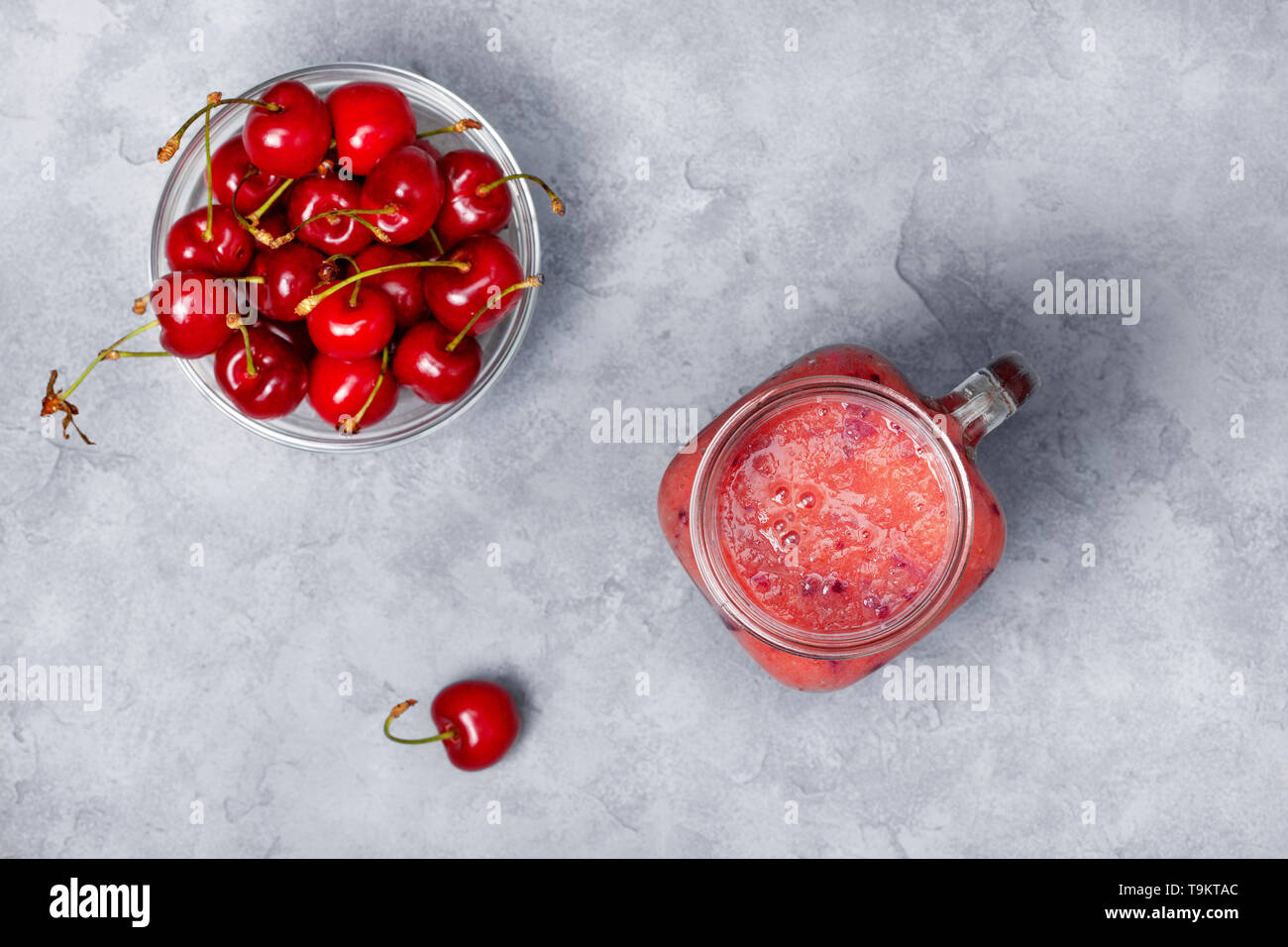 smoothies sweet cherry in a mason jar, fresh sweet cherry on a gray concrete background. view from above Stock Photo