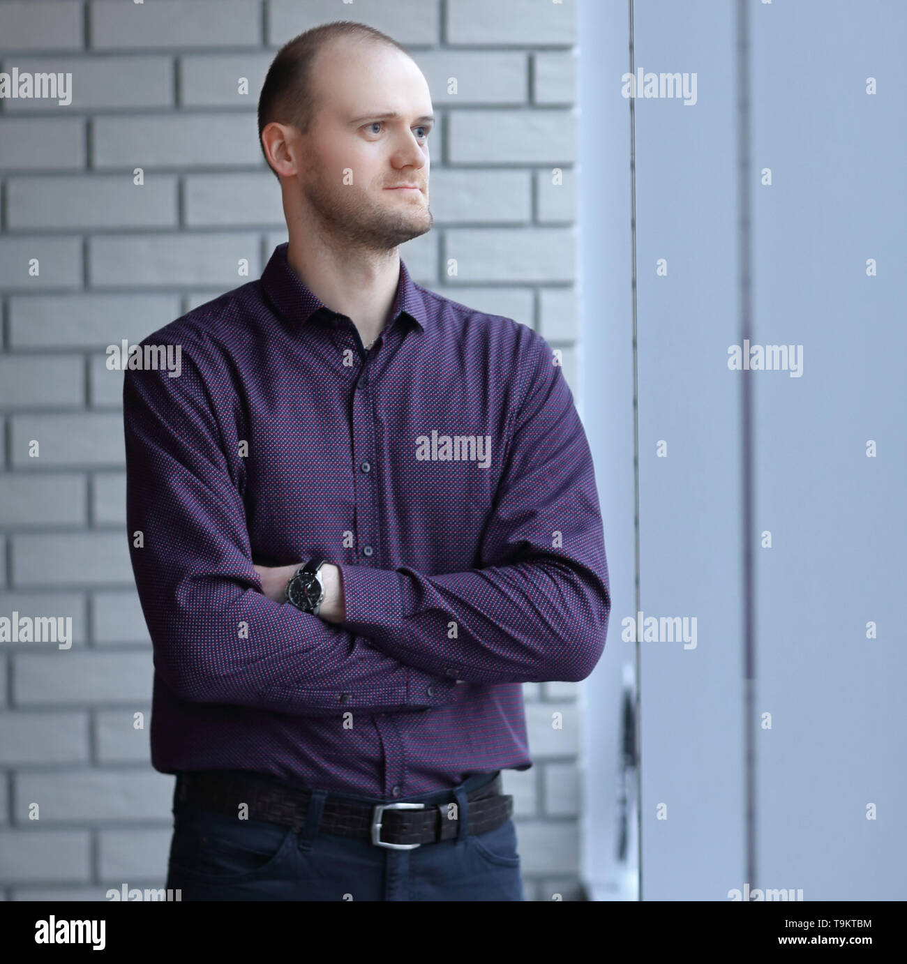 pensive businessman looking out office window.business people - Stock Image
