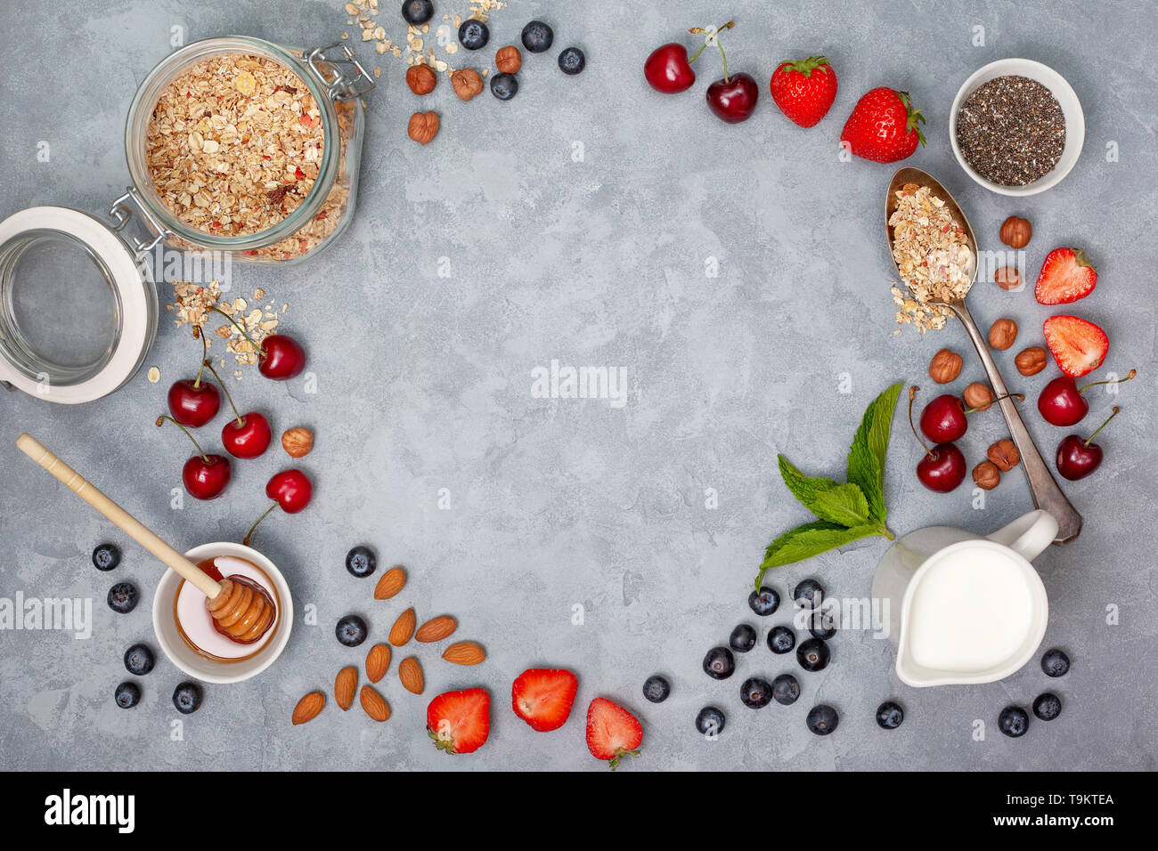 ingredients for breakfast: granola, chia seeds, fresh berries and nuts on a gray background. view from above. Stock Photo