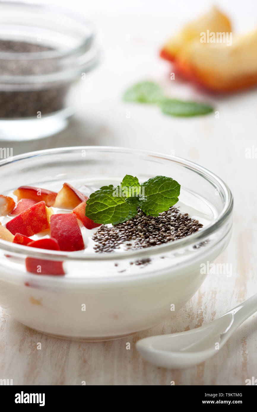 healthy breakfast. yogurt with peach pieces and chia seeds in a glass bowl on a white wooden background Stock Photo