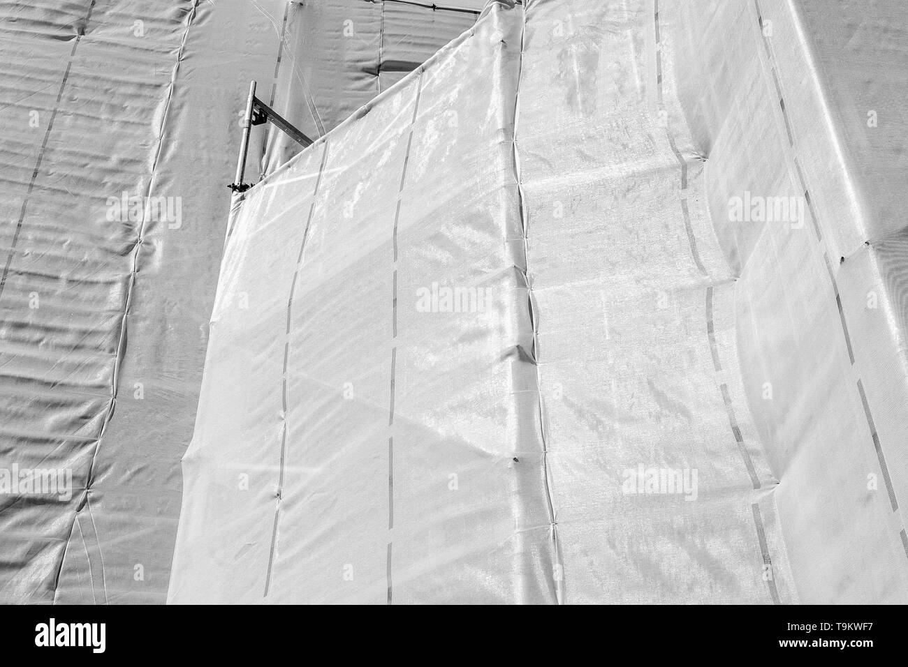 Plastic safety net and scaffolding around a building which is restored in black & white. - Stock Image