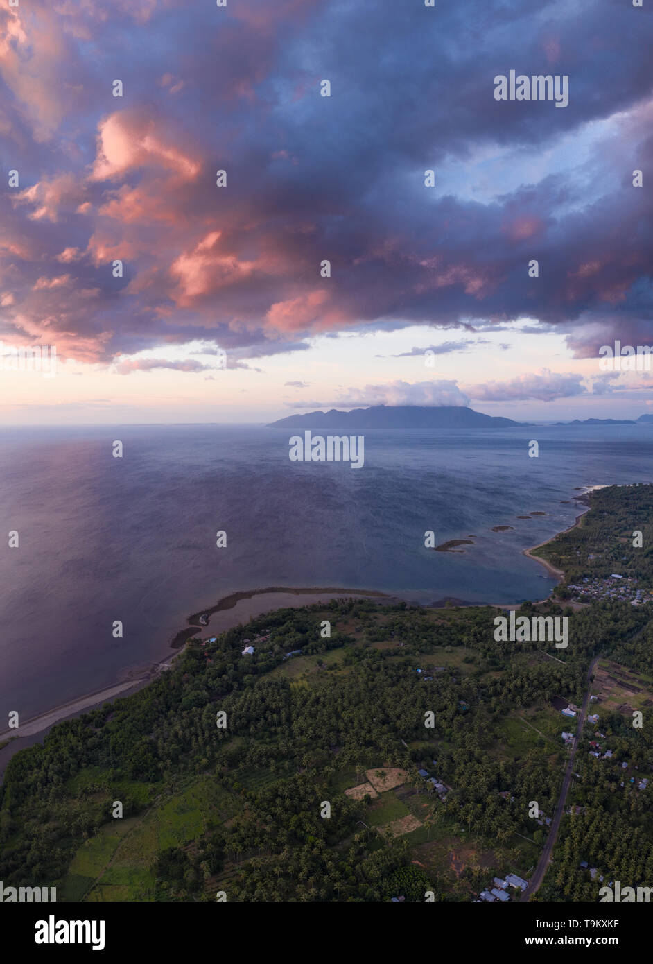Seen from an aerial view, the tropical island of Flores is illuminated at sunset. Flores is part of the Lesser Sunda Islands of Indonesia. - Stock Image