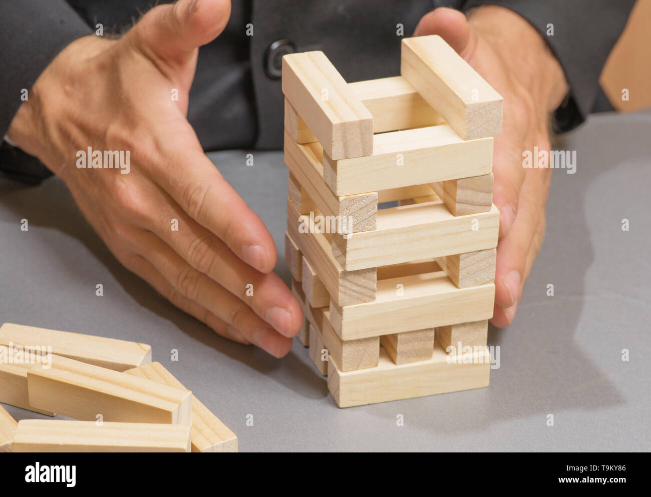 Hands Of A Young Businessman Building Towers Of Wooden Blocks
