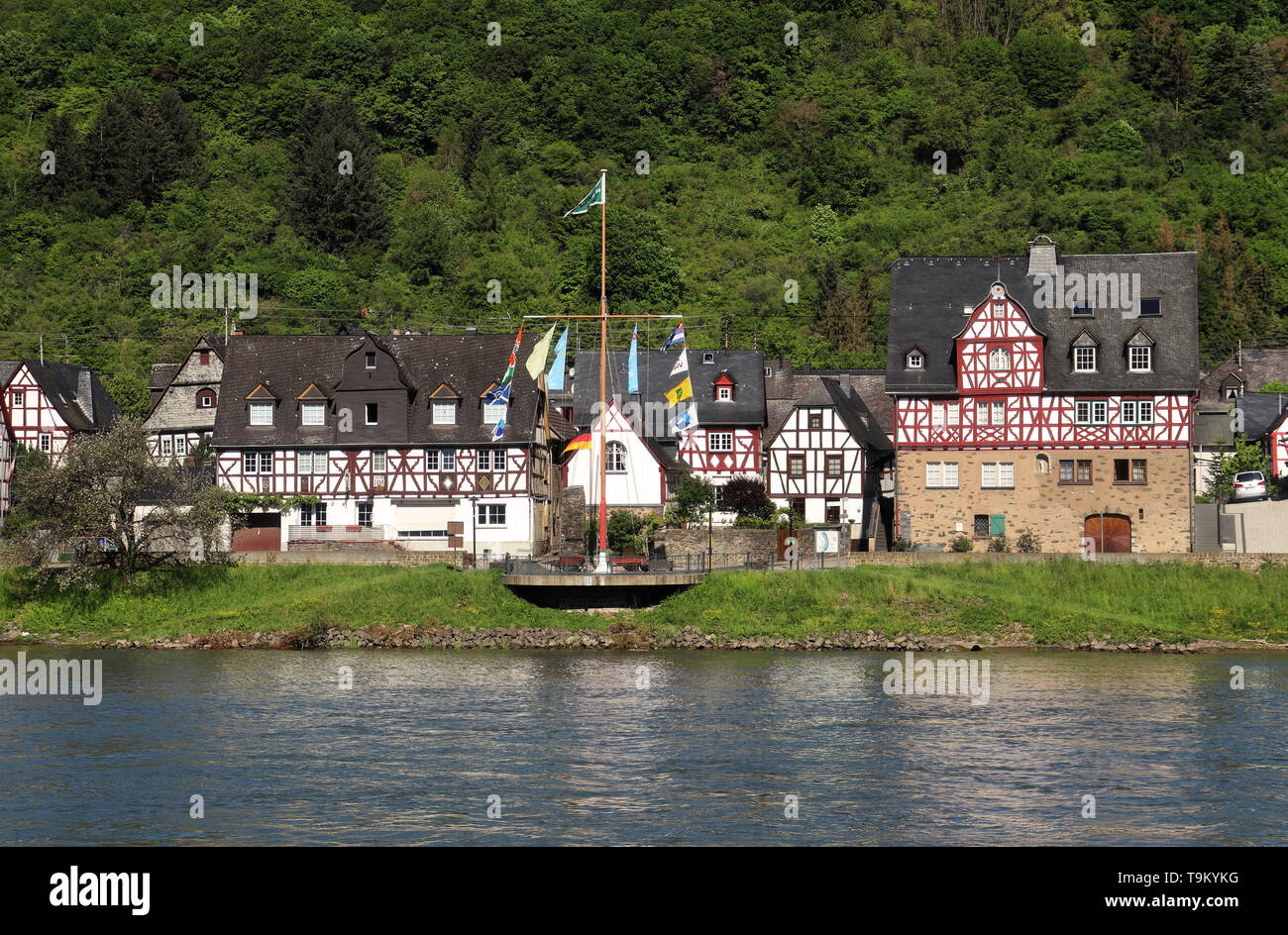 Riverside village on the Rhine river in Germany with tree covered Hill in the background - Stock Image