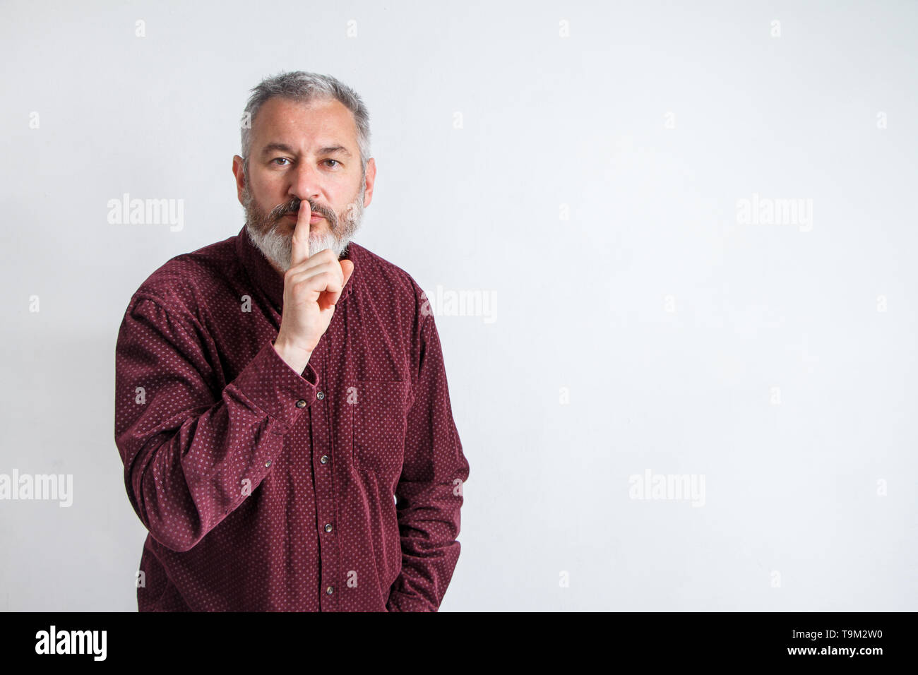 gray bearded man have the finger on lips as man gesturing shh sign, please be silent concept. - Stock Image