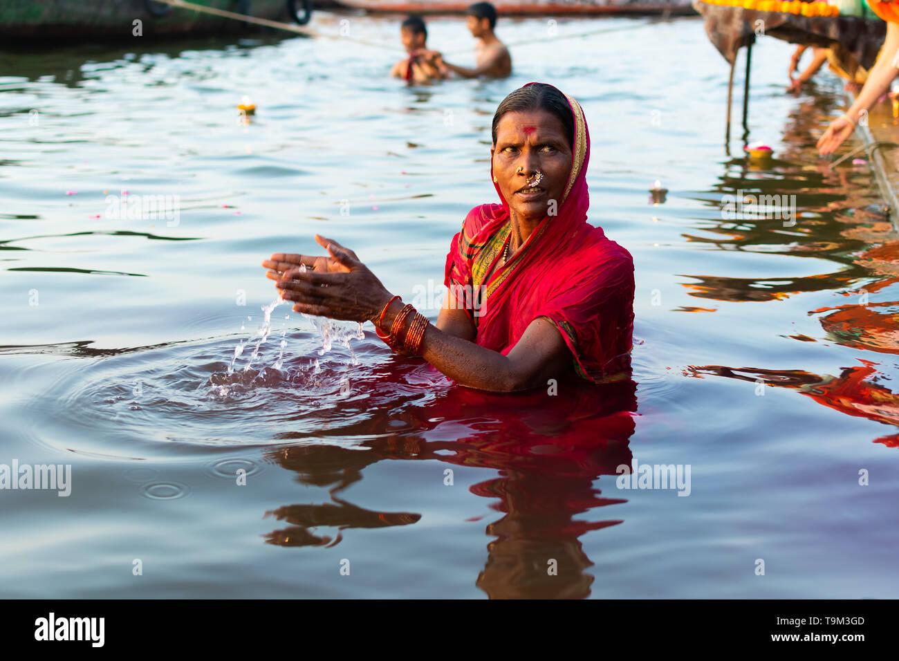 Varanasi, India, 27 Mar 2019 - Hindu woman in sari making offering to the gods in Ganga river at Varanasi, India - Stock Image