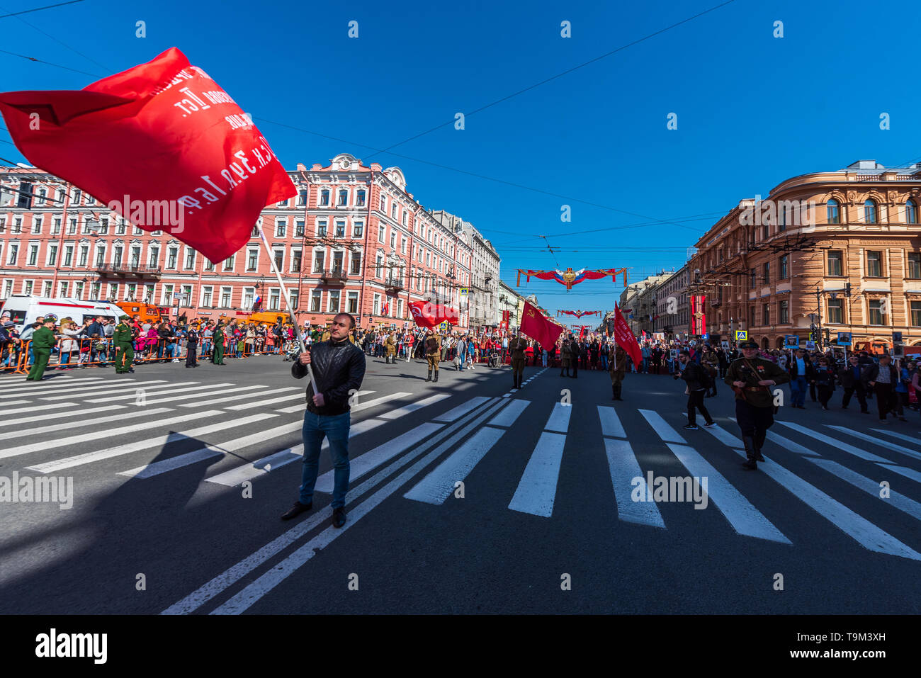 Immortal regiment - people carry banners of Soviet Union & comunism party, Victory Day, Nevsky Prospect, St. Petersburg, Russia - Stock Image